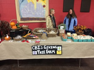 Allison and a coworker sell produce and handmade goods at the CBI Giving Farm stand at the Allen Farmers Market.